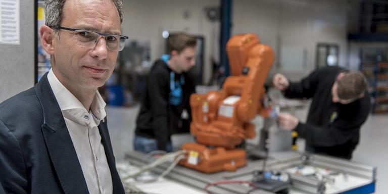 Directeur Menno Kooistra van STT. Op de achtergrond wordt gewerkt aan een zesassige robotopstelling voor automatische assemblage. Dit voorbeeld van van smart manufacturing zal worden gepresenteerd bij de opening van het bedrijf. Foto Geert Job Sevink