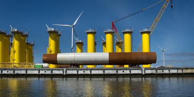Onderdelen voor windmolens wachten op de kade in de Eemshaven op transport naar zee.