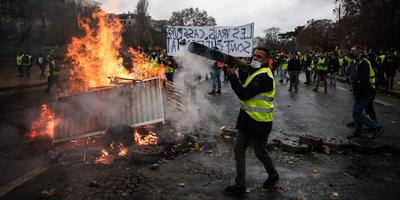 Wat de beweging van de Gele Hesjes (hier in Parijs) bindt is wantrouwen, 'tegen zo'n beetje alles'. Foto's: AFP, ANP en EPA