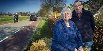 Annie en Jaap Lourens voor hun huis in Tolbert, met op de achtergrond de bocht waar het misging. De motorfiets kwam in drie delen ter hoogte van de boom in hun tuin tot stilstand. Foto Duncan Wijting