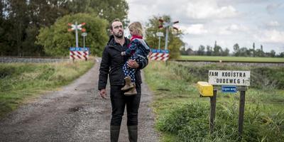 Boer Marcel Kooistra bij de spoorwegovergang die naar zijn boerderij leidt. Met het plan voor een nieuwe route is hij niet tevreden. foto Geert Job Sevink