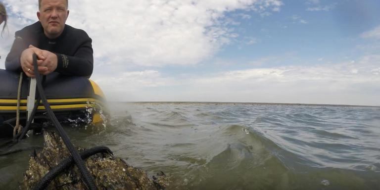 De achtersteven van het scheepswrak steekt soms boven het water uit. Op de foto groepslid Bert Kremer tijdens het onderzoek in 2015. Foto Ernie de Jonge