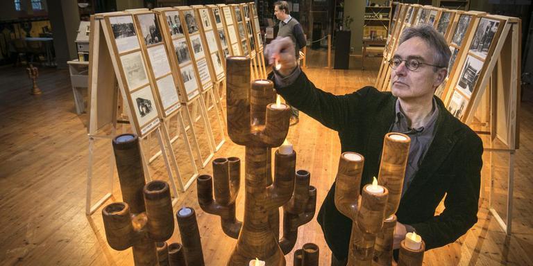 Marcel Wichgers van de Stichting Folkingestraat Synagoge laat een van de houten menora's zien bij de expositie Onze Stadse Joden van Pieter Oegema.