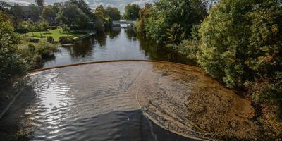 Na het lek van 2 oktober verspreidde zich een naar olie stinkende drab op het Afwateringskanaal in Farmsum. Pas na zes dagen werd vastgesteld dat het aardgascondensaat van het naburige NAM-tankenpark betrof. Foto: Archief Huisman Media