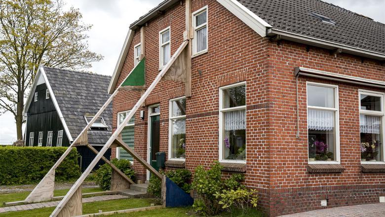 Een beschadigde woning wordt versterkt door stutten in Loppersum. Foto: ANP