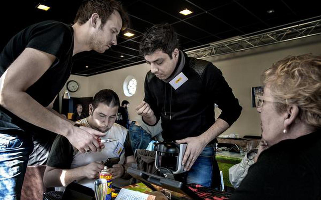 Trinette Blijham kijkt toe hoe haar koffieapparaat onder handen wordt genomen door vrijwiller Dick (links), Bashar (midden) en Dia. FOTO PETER WASSING