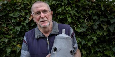 Jan Blaak met een door kogels doorboorde scheepsbel. Foto Jan Zeeman.