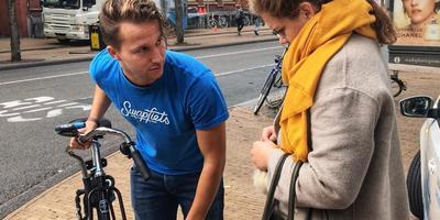 Daniël (24) legt Puck (19) uit hoe de lampjes op haar fiets werken.