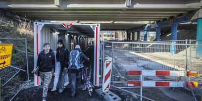 Fietsers en wandelaars kunnen de Zuidelijke Ringweg dinsdag nog passeren door een containertunnel langs de Helperzoom. Woensdag gaat de route dicht en kunnen fietsers weer aan de andere kant van het spoor langs de werkzaamheden. Foto: Jan Willem van Vliet
