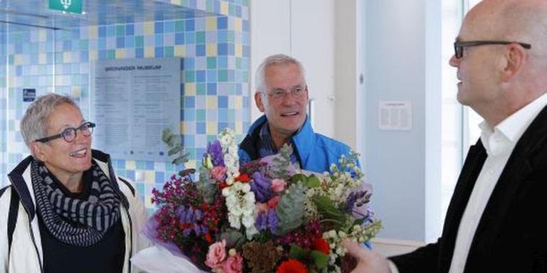 Foto: Museumdirecteur Blühm overhandigt de vijf miljoenste bezoeker een bos bloemen.