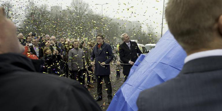 Wethouder Roeland van der Schaaf (rode sjaal) onthult het bouwbord met het ontwerp van de nieuwe studentenflat aan de Friesestraatweg.