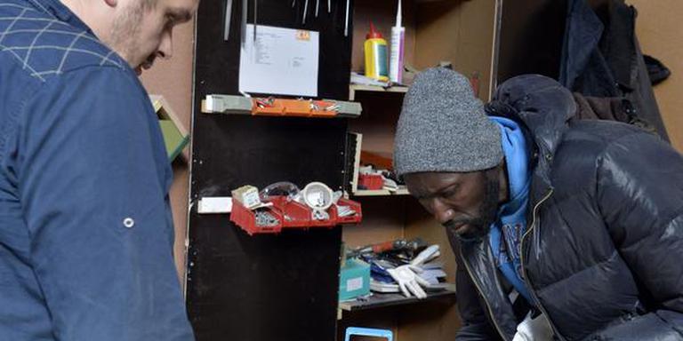 Cursusleider Jan Sanders begeleidt asielzoeker Charley op de cursus houtbewerking. FOTO BODEWIJN BENTING