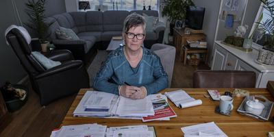 Lida Riedstra met de grote hoeveelheid paperassen die inmiddels een hoofdpijndossier vormen. Foto: Jan Zeeman