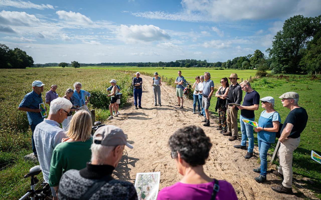 Leden van het Land van Ons luisteren naar de uitleg van gids Jan Wittenberg. De coöperatie wil de biodiversiteit bevorderen en natuurbewust landbouwen. Links staat boekweit, de gekochte grond loopt tot het maïs in de verte.