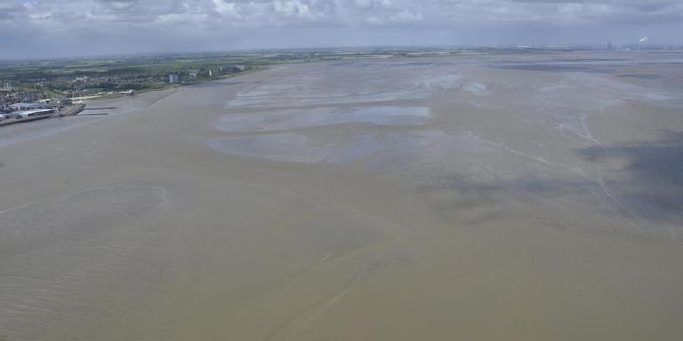 Blik over de Eems en Dollard, met links Delfzijl en op de achtergrond de Eemshaven: 'invang' en afzet van baggerslib kan de kwetsbare natuur helpen om zich te herstellen van industrie, scheepvaart en ander menselijk ingrijpen. Foto Rijkswaterstaat