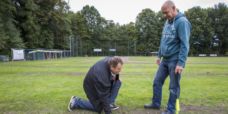 De bestuursleden Ronald Kingma (links) en Will Valentijn inspecteren het vernielde honkbalveld. FOTO HUISMAN MEDIA