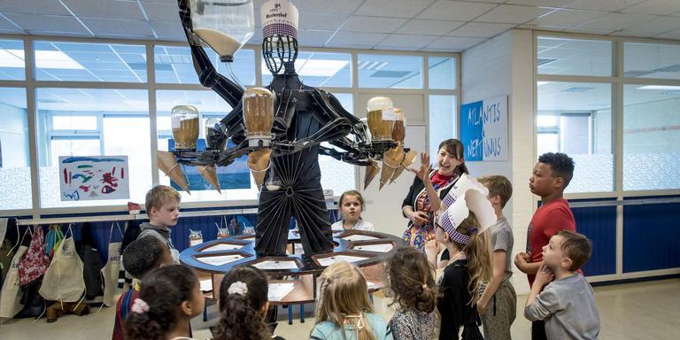Kinderen testen de Smaakmaker, een robot die zoutarme kruiden in zakjes strooit.