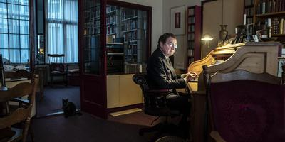Jean Pierre Rawie achter zijn bureau, aan het werk. Foto Reyer Boxem