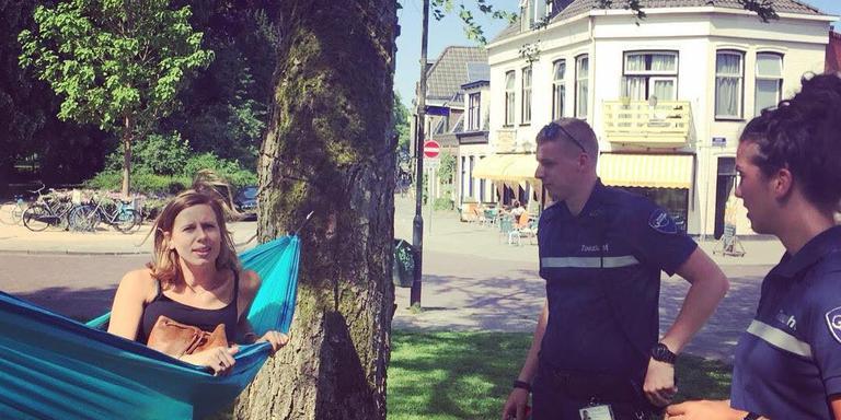 Handhavers van de gemeente sommeren Eline Kamminga om haar hangmat weg te halen.