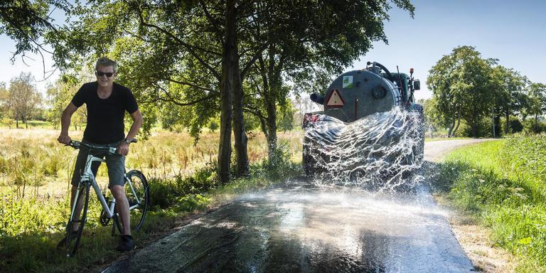 Aan de Hoornsedijk is waterschap Noorderzijlvest bezig met het nat houden van de dijk tegen uitdroging. Foto Reyer Boxem