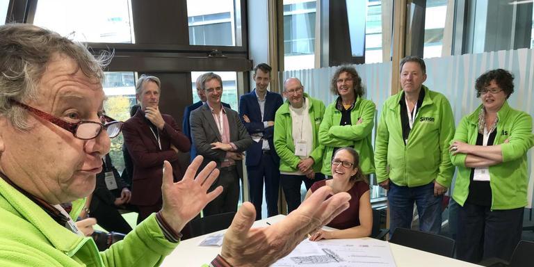 Voorzitter Piet Hazekamp van Paddepoel Energiek spreekt p de Noordelijke Klimaattop alle partners toe, vlak voordat gedeputeerde Nienke Homan (GroenLinks, zittend) de afspraken ondertekent. Rechts vice-voorzitter Els Struiving die naar de Wereld Klimaattop van de VN gaat. Foto: DvhN