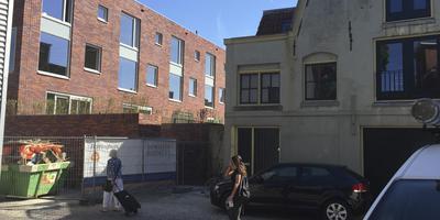 De achtergevel en tuinen van vijf woningen gaan straks schuil achter een blinde muur van vijftien meter hoog. Rechts het pakhuis dat tegen de vlakte gaat. FOTO DVHN