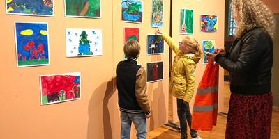 Anne-Rins (10) vergelijkt haar schilderij met die van haar klasgenoten.