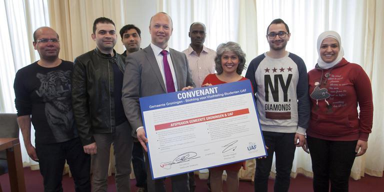 Wethouder Ton Schroor en UAF-directeur Mardjan Seighali (midden) met enkele vluchteling-studenten uit Groningen. FOTO RENÉ KEIJZER