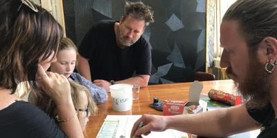 De familie Boonzaayer is onder de indruk van het verhaal van kunstenaar Wouter Nijland (rechts).