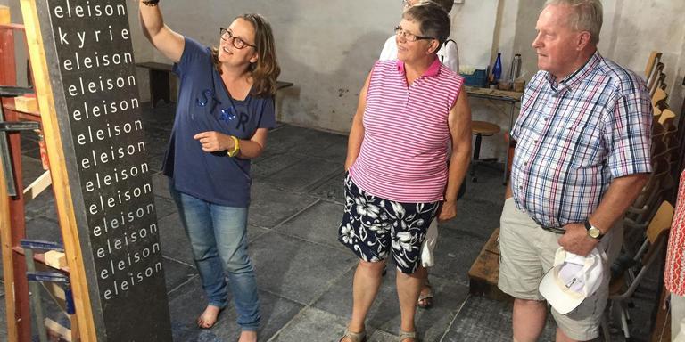 Beeldhouwer Anjet van Linge (links) toont haar kunstwerk voorin de kerk van Eenrum aan bezoekers. Foto DvhN