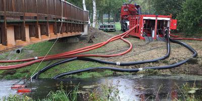 Met een pomp haalde de brandweer water uit de Nordradde om de veenbrand te blussen. Foto EPA/Focke Strangmann