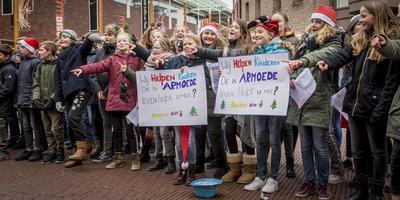 Leerlingen van basisschool De Starter zingen kerstliedjes om geld in te zamelen voor Groningse kinderen die in armoede leven. Foto Geert Job Sevink