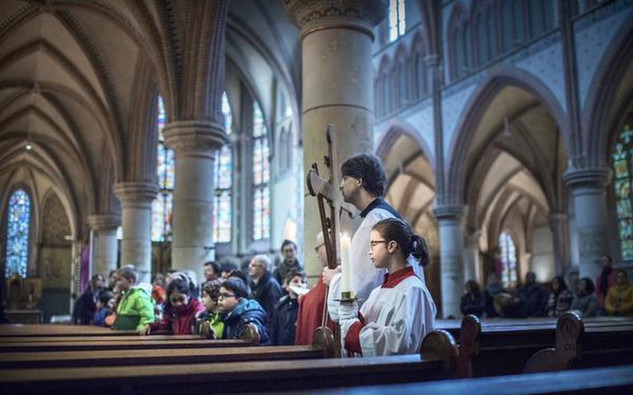 In de Jozefkerk vertelt Pastoor Rolf Wagenaar kinderen het lijdensverhaal. FOTO CORNE SPARIDAENS