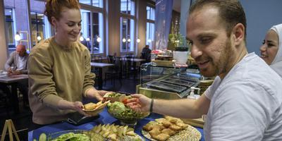 In leescafé Belcampo in Groningen serveert kok Mustafa Taleb zijn Iraanse hapjes. Foto: Jan Zeeman