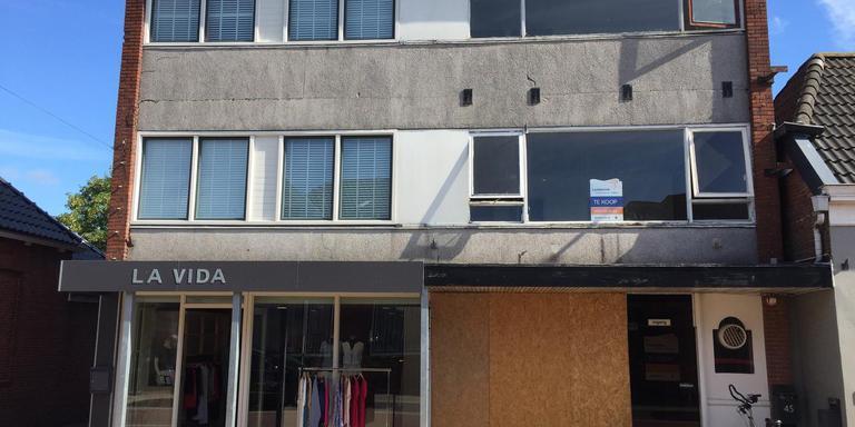 Modeboetiek La Vida (links) die morgen sluit met rechts het zwaar gebrekkig onderhouden pand van een voormalig Chinees restaurant. Foto DvhN
