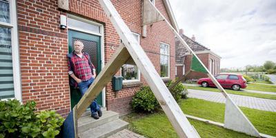 Een bewoner voor zijn beschadigde woning in Loppersum . Foto: Archief DvhN/ANP Jerry Lampen