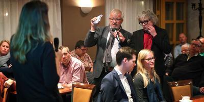 Wethouder Anja Woortman (op de rug) luistert naar een inwoner. Projectleider versterking Midden-Groningen, Nico Beukema, houdt de microfoon vast.Foto: Harry Tielman
