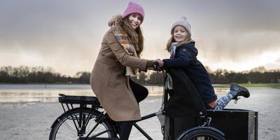 Suzanne de Jong en dochter Lise met hun elektrische bakfiets. FOTO REYER BOXEM