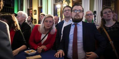 Gedeputeerde Eelco Eikenaar en Tweede Kamerlid Sandra Beckerman van de SP luisteren naar de eerste exitpoll tijdens de centrale uitslagenavond van de Provinciale Statenverkiezingen in het Groningse provinciehuis. foto ANP