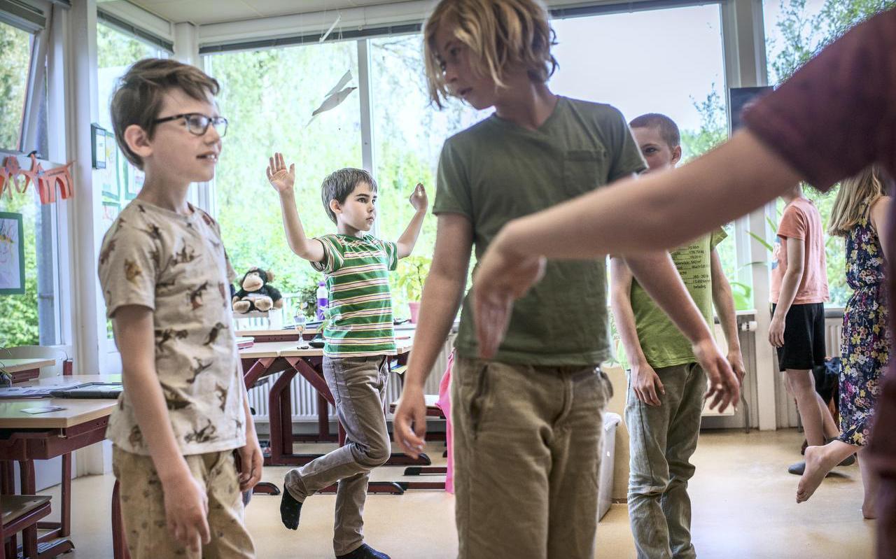 Op basisschool 't Hoogholtje in Wehe-den Hoorn doen kinderen onder leiding van oefentherapeute Petra Weel oefeningen tegen 'gameboyrug'. FOTO CORNÉ SPARIDAENS