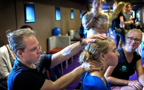 John Molenaar van Massage Praktijk Groningen masseert een KEI-loper tijdens Love, Lust & Lounge in Pathé. Foto Peter Wassing