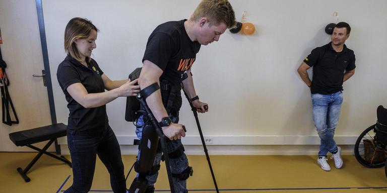 Dennie Jager uit Wagenborgen kan na twee jaar in de rolstoel lopen dankzij het exoskelet. Met zijn begeleidster Mandy Smidts op de hielen liep hij vorig jaar de eerste openbare stappen.