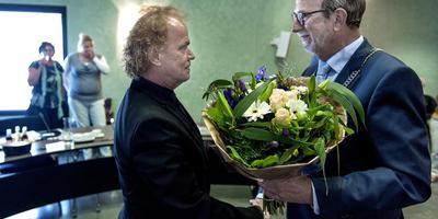 Burgemeester Rinus Michels feliciteert nieuwbakken raadslid Arie Molenhuis. FOTO DVHN