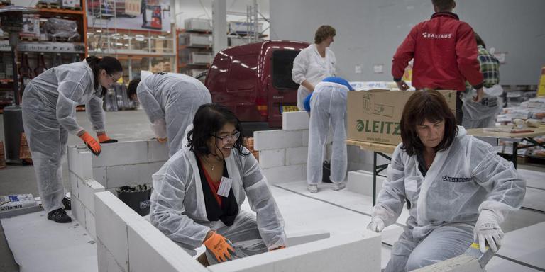 Chanchal van der Mee en Petra Knip bouwen samen een binnenmuur. FOTO JASPAR MOULIJN