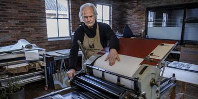 Grafisch ontwerper Geert de Koning uit Ten Post drukt het bijbelboek Openbaringen. Foto: Jan Zeeman