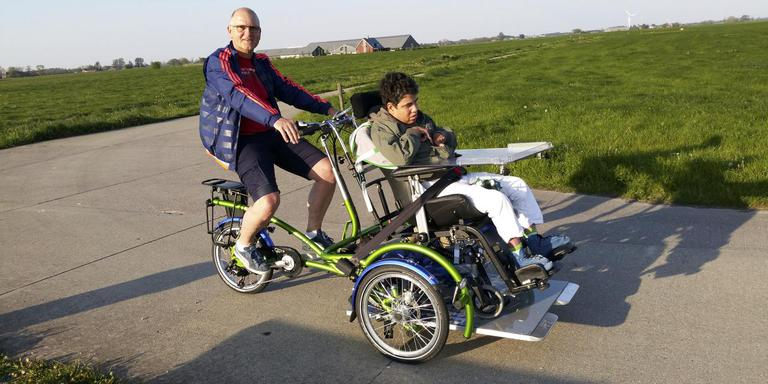 Arjan Kloeze van Wielervereniging Bedum met de rolstoelfiets op pad met Jorda Koperberg. FOTO DVHN