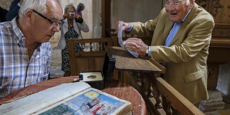 In de kerk van Krewerd staat Edze de Boer (rechts) op het punt om te gaan spreken. Links kijkt een belangstellende naar de botjes van Haterbrand. foto: Jan Zeeman