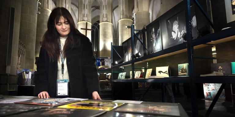 Avalon Peters van Mojo Concerts bekijkt muziekparafernalia in de Martinikerk. De tentoonstelling is vrijdag nog te bezoeken, zaterdag worden de objecten geveild. Foto Peter Wassing
