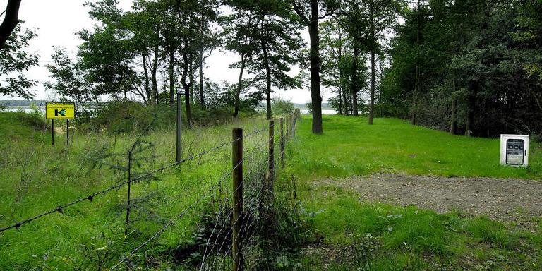 Een hek op de camping De Papaver stond enige tijd symbool voor de slechte verhouding tussen de campingbaad (rechts zijn grond) en de zandwinner. Foto: Archief DvhN