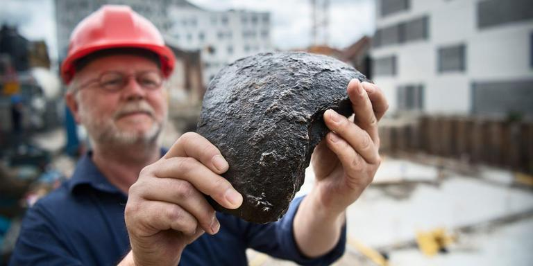 Stadsarcheoloog Gert Kortekaas met een scherf van een soortgelijke bom die onder het Groninger Forum is gevonden. Foto: Corné Sparidaens